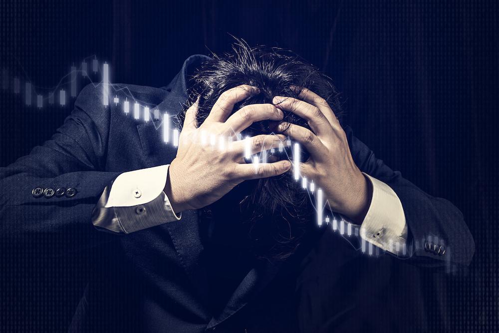 ビジネスイメージ 株式チャート下落 頭を抱える男性