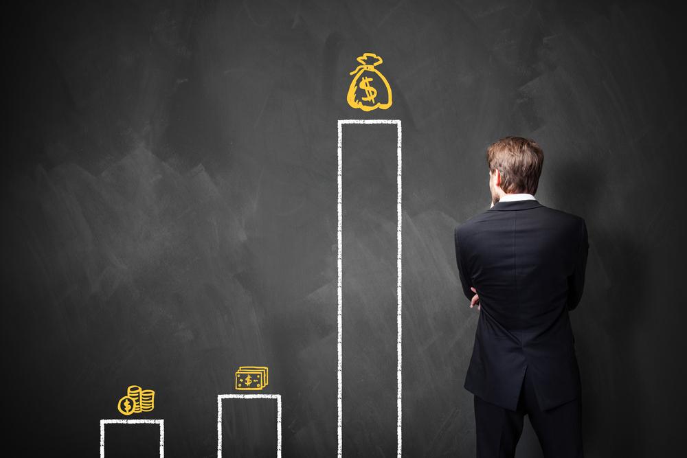 管理費・修繕費が高すぎないかグラフを見ながら考える男性の後ろ姿