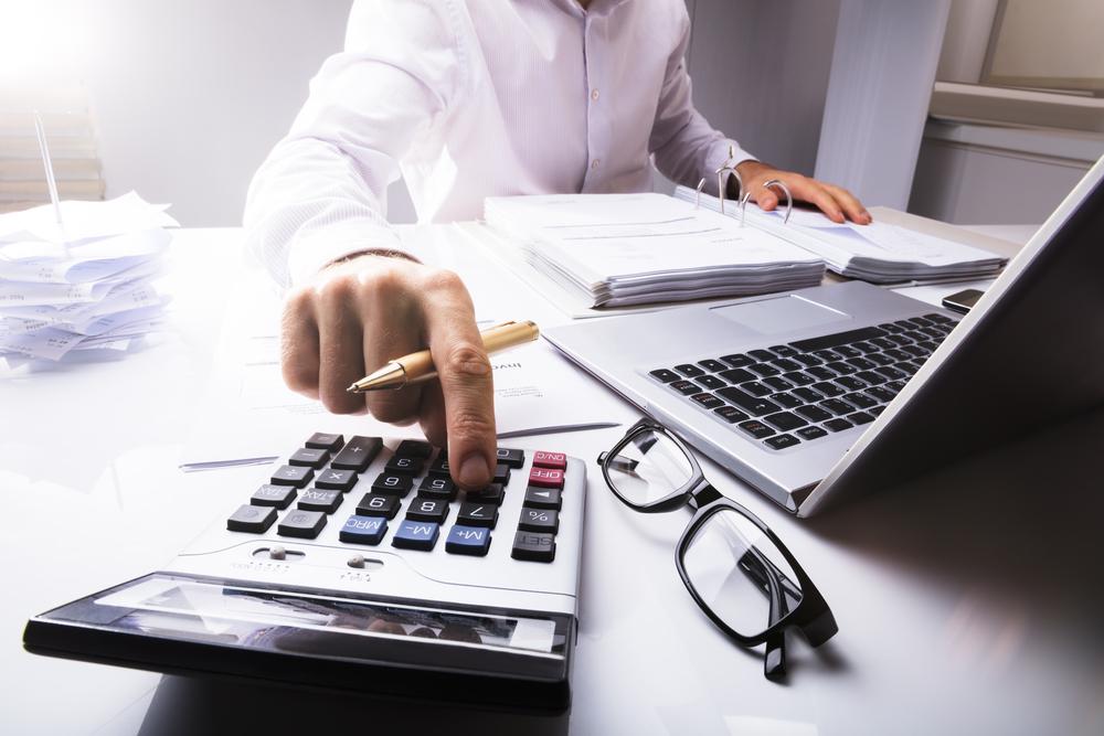不動産投資と株式投資のランニングコストをパソコンと電卓で計算する男性