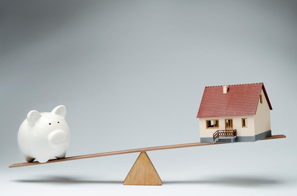 家賃と担保価値のバランスを表した家と豚の貯金箱