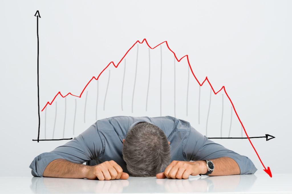 不動産投資で価格の下落に落ち込む男性