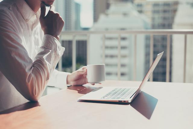 コーヒーを飲みながらパソコンで不動産投資のデメリット・リスクについて考え調べる男性