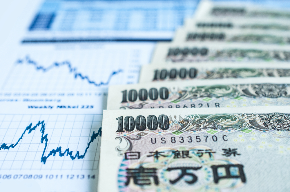 不動産投資と株式投資の変動リスクを比較しているグラフと日本の一万円札