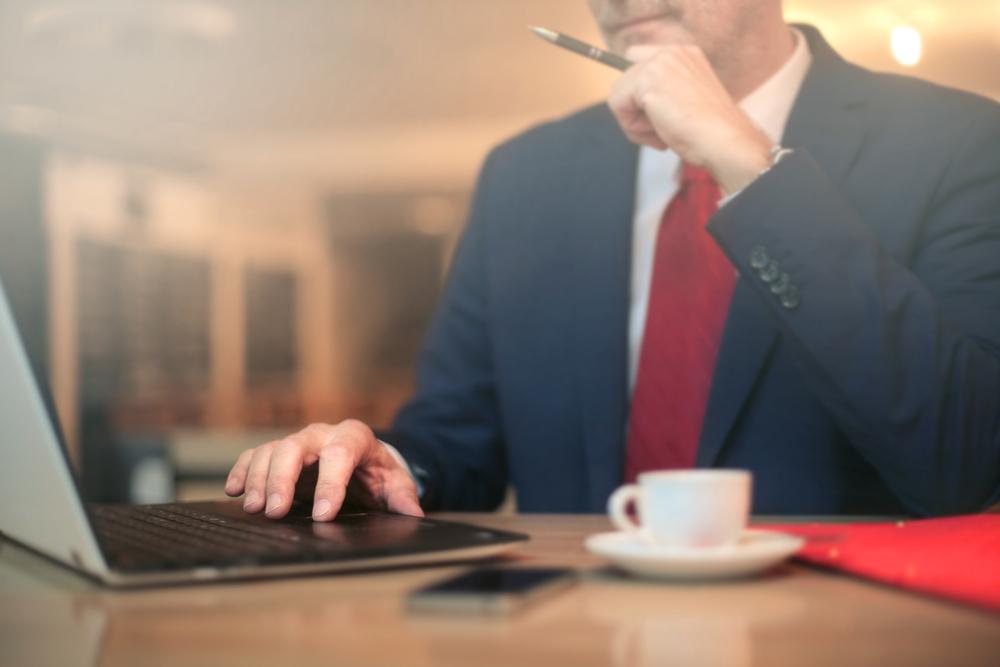 投資計画をパソコンで立てる男性