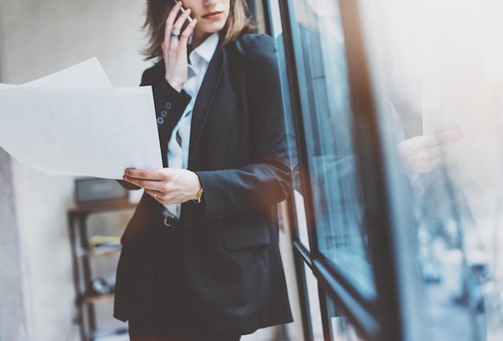 資料を見ながらスマートフォンで電話をする女性