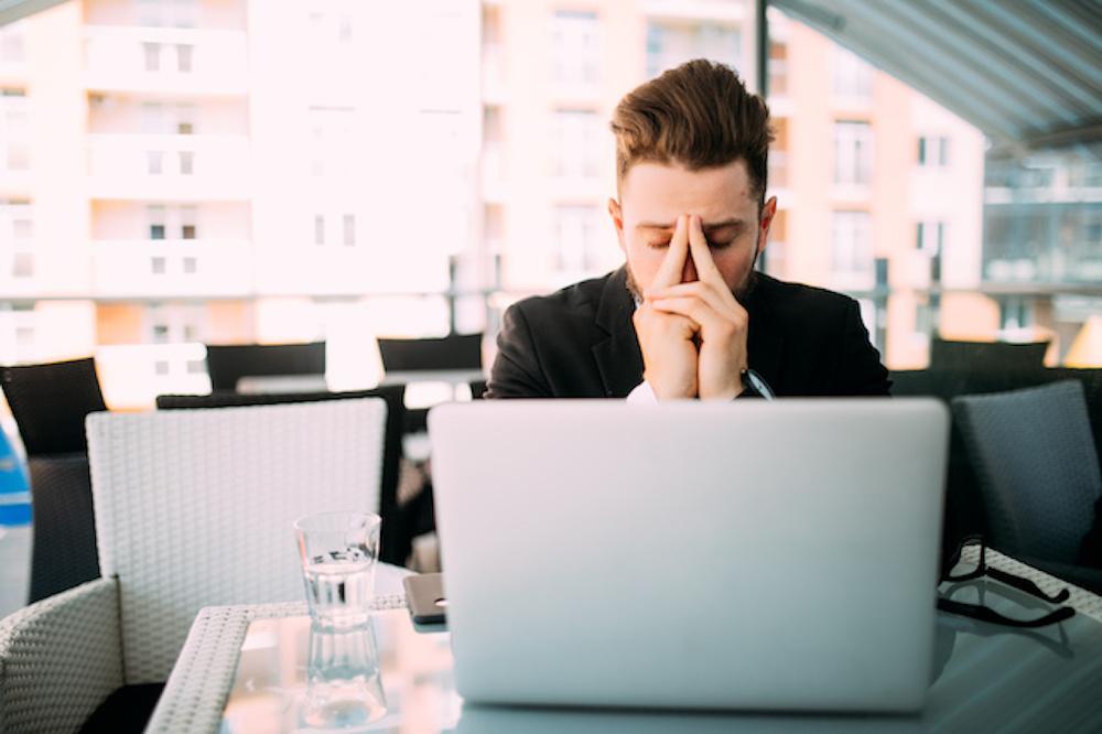 ノートパソコンを前に悩む男性