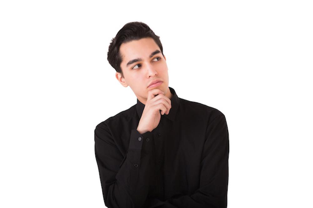 黒のニットを着た悩む男性