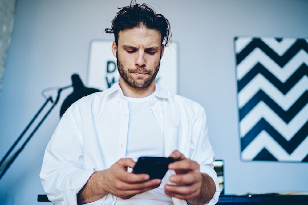 スマートフォンを見ながら悩む男性