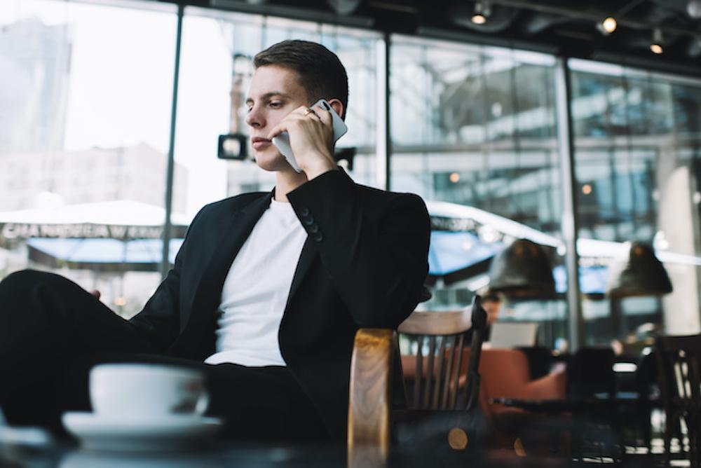 カフェでスマートフォンで電話をするスーツ姿の男性