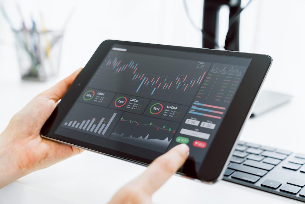 タブレットで株の変動グラフを見ている人の手