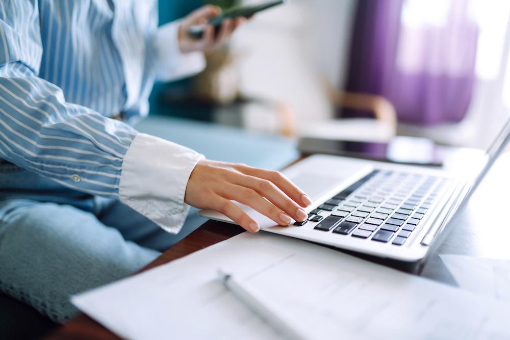 ノートパソコンをいじりながらスマートフォンをいじる女性の手