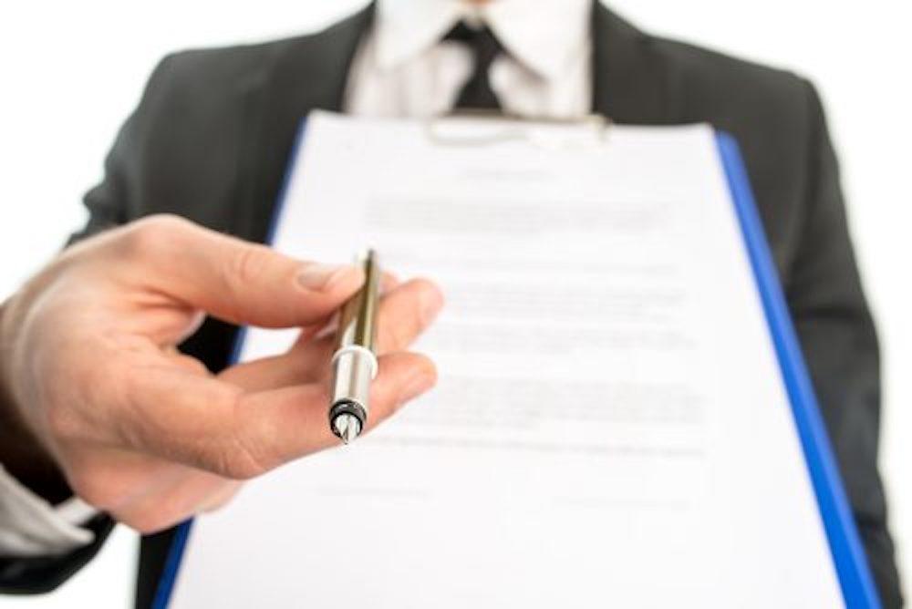 書類にサインを求めるペンを持つ男性