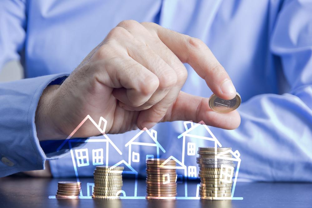 3つの家にお金を積み上げる男性の手