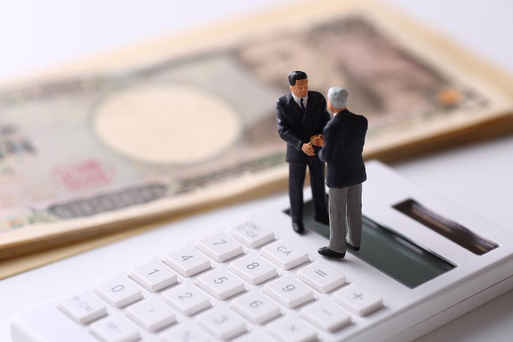 日本円一万円札 電卓 スーツ姿の男性模型二人