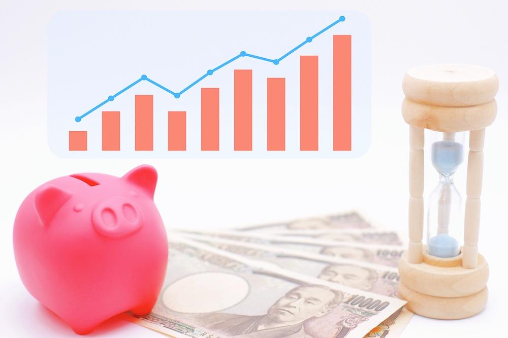 ピンクの貯金箱と1万円札と上昇のグラフ