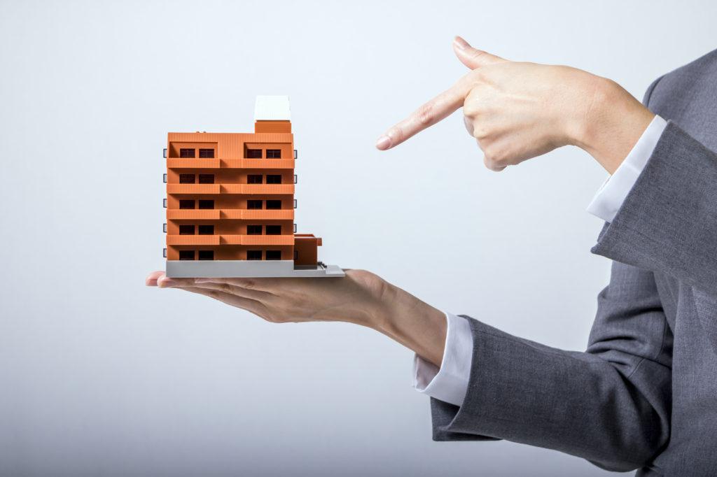 アパートの模型を手のひらの上に乗せて指を指す男性
