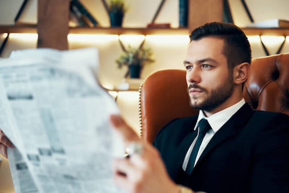 新聞を読むスーツ姿の男性