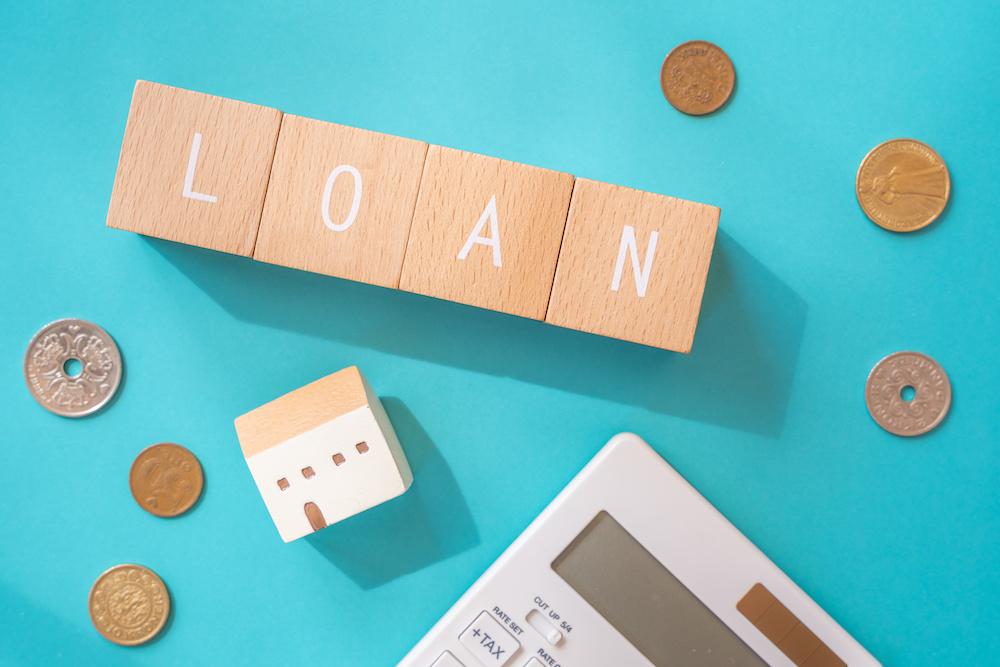 住宅ローン|「LOAN」と書かれた積み木ブロックとおもちゃの家と電卓と小銭